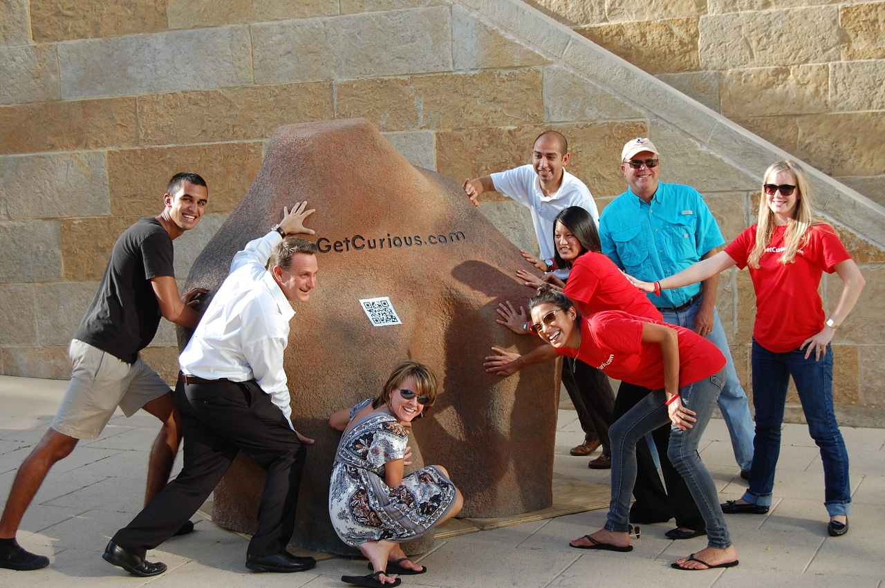 "Rich Phillips (front left) with his Austin team with one of the Get Curious campaign ""rocks."""